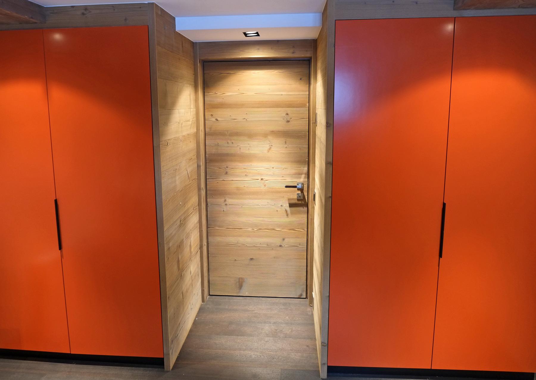 Armoires laquées orange, et porte en sapin sablé